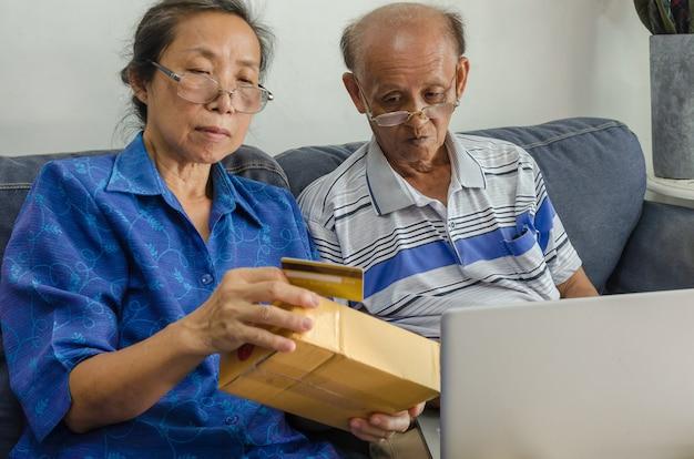 Dwie starsze osoby azjatyckie, zakupy online. starszy posiadania karty kredytowej siedzi na kanapie z laptopem w domu.