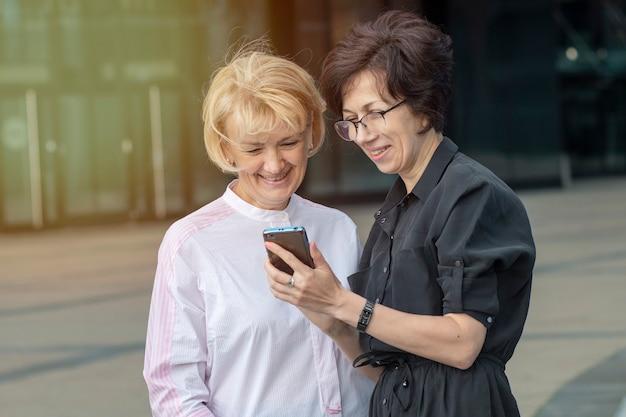 Dwie starsze szczęśliwe kobiety patrząc na smartfona i uśmiechnięte