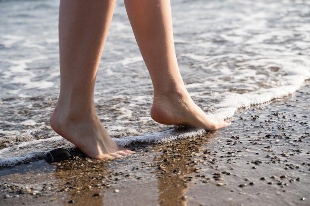 Dwie stopy na piasku, gdy obmywają je fale. zastosowano ciepły filtr.