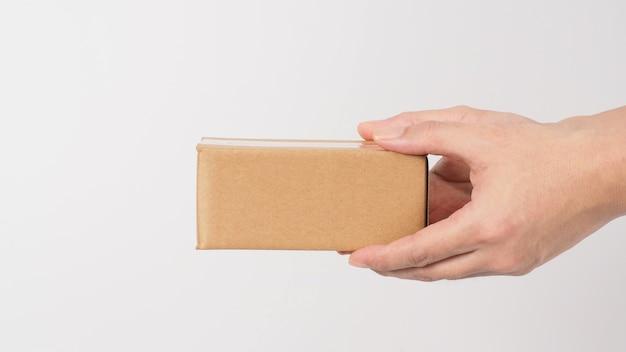 Dwie strony trzyma brązowe pudełko na białym tle.