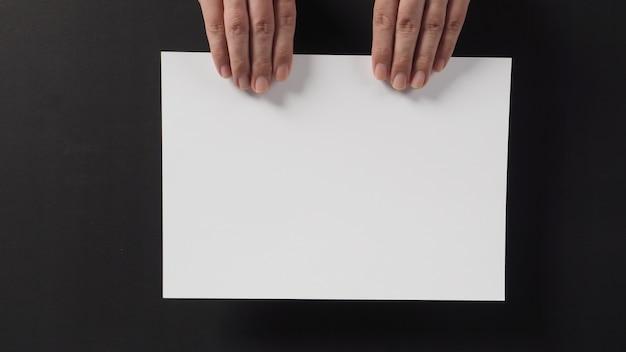 Dwie strony trzyma pusty pusty papier a4 na czarnym tle.