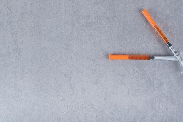 Dwie strzykawki z brązowym płynem na szarej powierzchni
