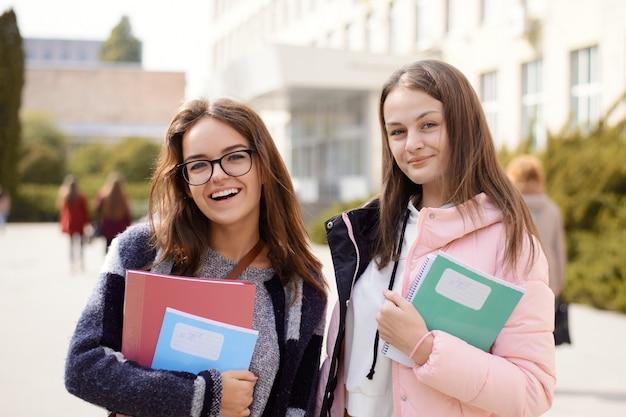 Dwie studentki przed budynkiem uniwersytetu trzymania książek