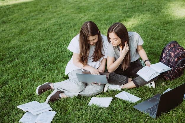 Dwie studentki siedzą w parku na trawie z książkami i laptopami, ucząc się i przygotowując do egzaminów. kształcenie na odległość. miękka selektywna ostrość.