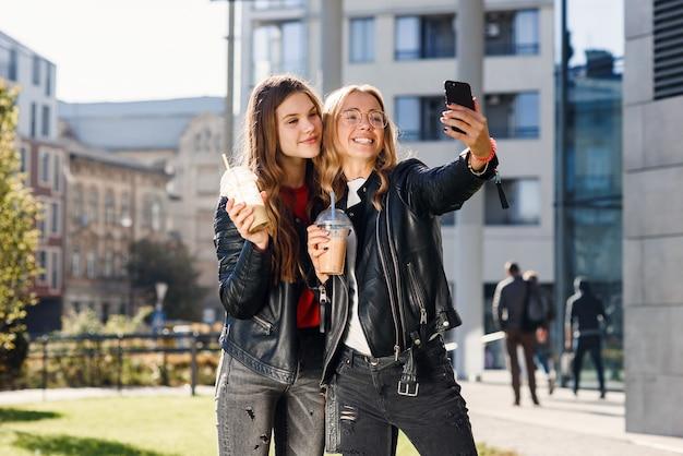 Dwie stylowe atrakcyjne nastolatki z smoothie i smartfonem w pobliżu centrum handlowego. czas wolny z najlepszymi przyjaciółmi.