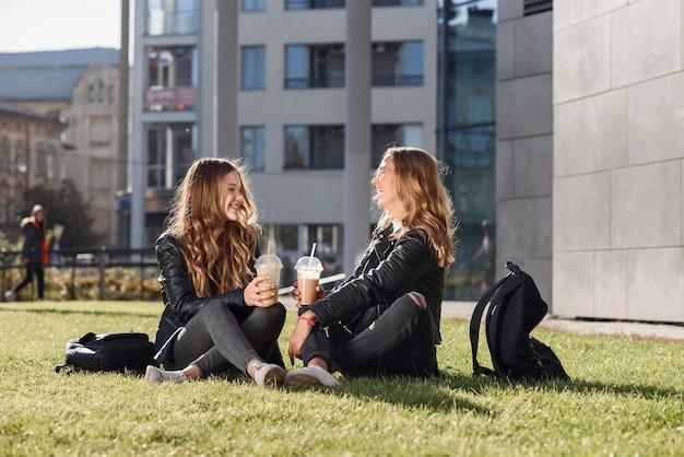 Dwie stylowe atrakcyjne nastolatki z smoothie i smartphone, siedząc na trawie. czas wolny z najlepszymi przyjaciółmi.