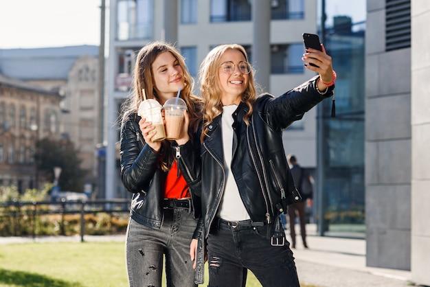 Dwie stylowe atrakcyjne nastoletnie dziewczyny z smoothie i smartfonem robiącym selfie. spędzanie wolnego czasu z najlepszymi przyjaciółmi.