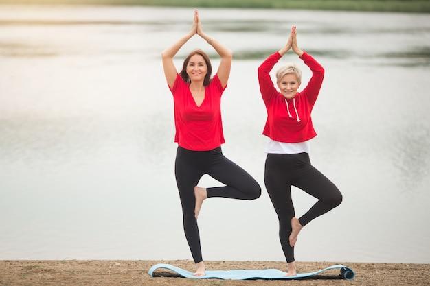Dwie stylowe dorosłe kobiety uprawiają latem sporty na świeżym powietrzu w pobliżu jeziora