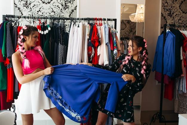 Dwie stylowe dziewczyny wybierają jedną niebieską sukienkę w sprzedaży i gniewnie ją ciągną.