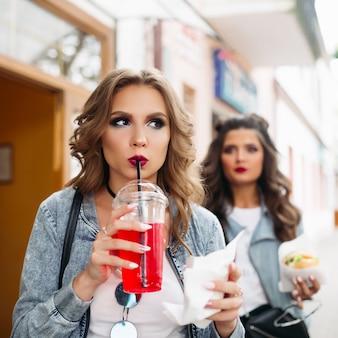 Dwie stylowe dziewczyny z łupem chodzące na ulicy z fast foodem i napojami.