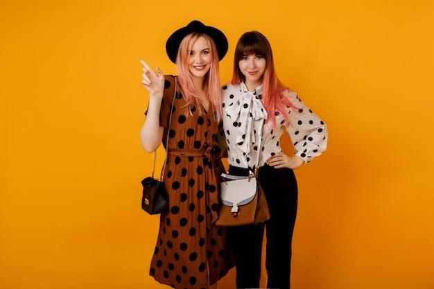 Dwie stylowe eleganckie kobiety w sukienkach pozujących na żółtej ścianie