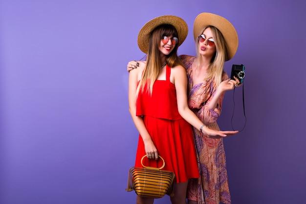 Dwie stylowe hipster dziewczyny bawiące się razem, czapki i akcesoria do sukienki w stylu boho w stylu vintage, blondynka robi zdjęcia swojej najlepszej przyjaciółce,