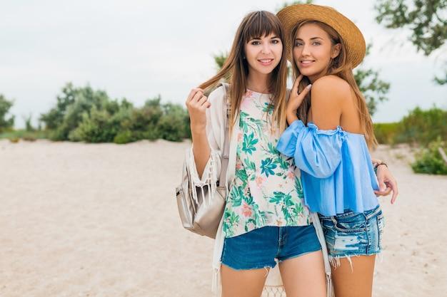 Dwie stylowe, ładne uśmiechnięte kobiety na wakacjach na tropikalnej plaży, przyjaciele podróżują razem