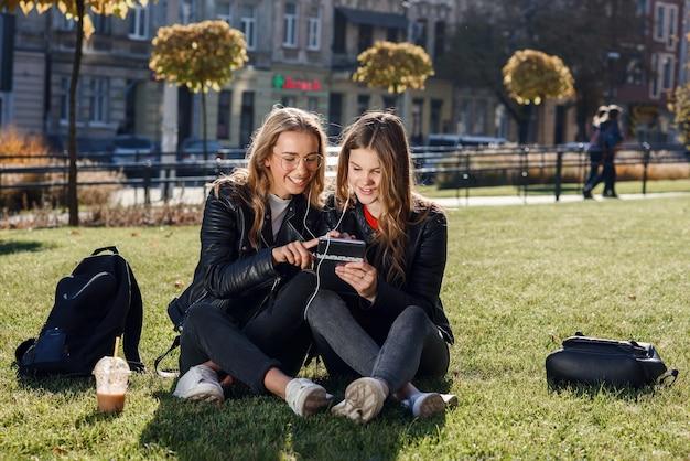 Dwie stylowe nastolatki z smoothie i smartphone, siedząc na trawie