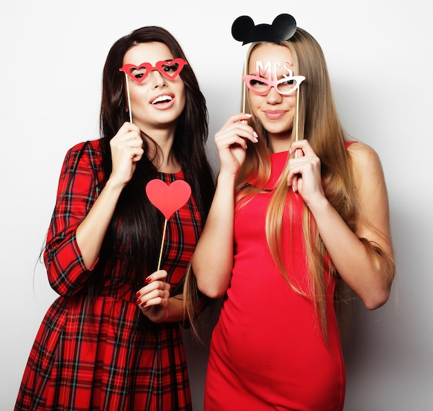 Dwie stylowe seksowne dziewczyny najlepsze przyjaciółki w czerwonej sukience gotowe na imprezę, na białym tle