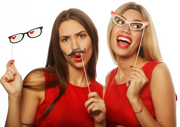 Dwie stylowe seksowne dziewczyny najlepsze przyjaciółki w czerwonej sukience gotowe na przyjęcie, na białym tle