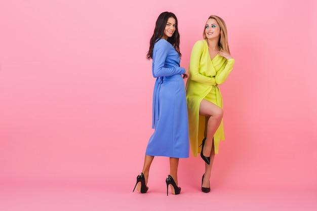 Dwie stylowe seksowne uśmiechnięte atrakcyjne kobiety pozujące pełnej wysokości na różowej ścianie w stylowych kolorowych sukienkach w kolorze niebieskim i żółtym, wiosenny trend w modzie
