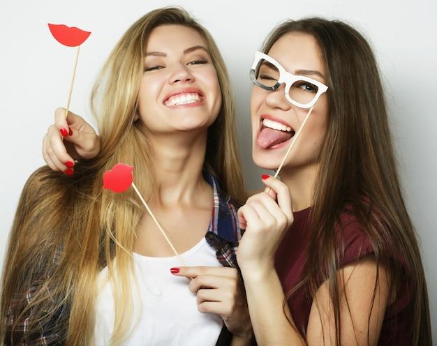 Dwie stylowe sexy hipster dziewczyny najlepsi przyjaciele gotowi na imprezę, na szarym tle