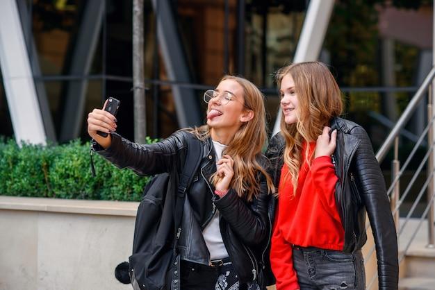 Dwie stylowe szczęśliwe nastoletnie dziewczyny ze smartfonem co selfie w pobliżu stylowego, nowoczesnego budynku na ulicy.