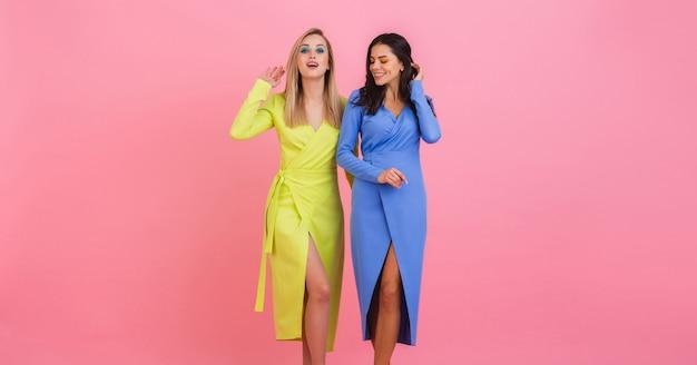 Dwie stylowe uśmiechnięte atrakcyjne przyjaciółki pozujące na różowej ścianie w stylowych kolorowych sukienkach w kolorze niebieskim i żółtym, wiosenny trend w modzie