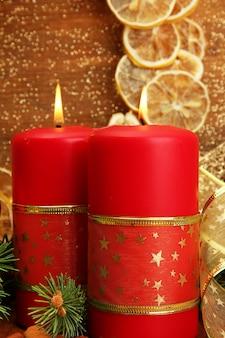 Dwie świece i ozdoby świąteczne na złotej powierzchni