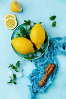 Dwie świeże cytryny w niebieskim talerzu na turkusowym tle betonu. tło żywności. widok z góry.