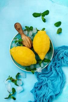 Dwie świeże cytryny w niebieskim talerzu na turkusowym tle betonu. tło żywności.