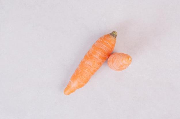 Dwie świeże marchewki na białym stole.