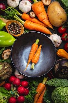 Dwie świeże marchewki zagrodowe w misce vintage i różne organiczne warzywa na rustykalne czarne tło betonu. jesienne zbiory, wegetariańskie jedzenie lub gotowanie koncepcji czystego zdrowego posiłku, widok z góry