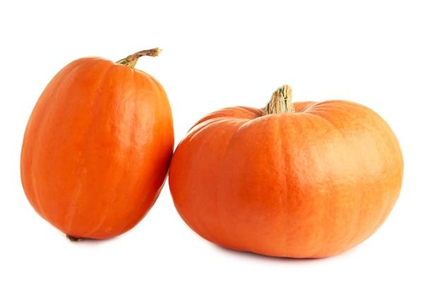Dwie świeże pomarańczowe dynie na białym tle
