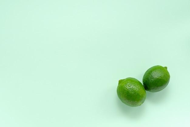 Dwie świeże soczyste limonki na delikatnym miętowym tle