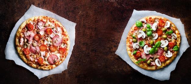 Dwie świeże włoskie pizze z pieczarkami, szynką, pomidorami, serem, oliwką, bazylią, na papierze podkładowym.