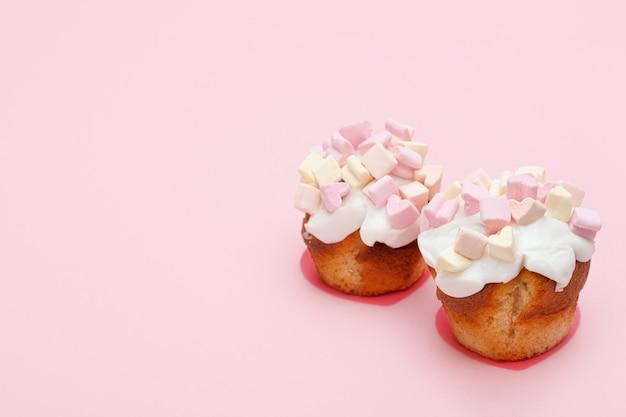 Dwie świeżo upieczone babeczki pokryte słodkim lukrem i piankami w kształcie serca na różowym tle. miejsce na tekst. walentynki