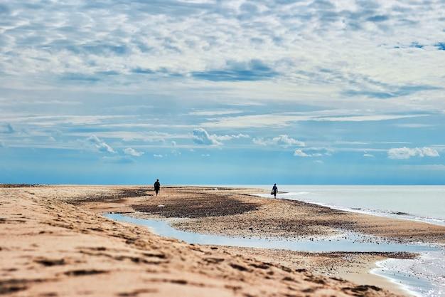 Dwie sylwetki na słonecznej plaży pod błękitnym niebem