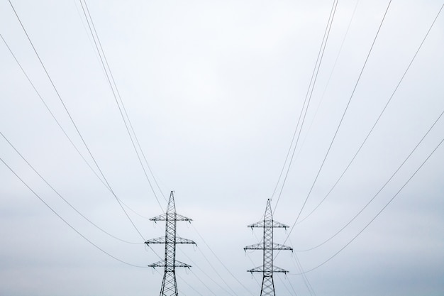Dwie symetryczne metalowe wieże elektryczne z drutami