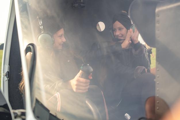 Dwie sympatyczne dziewczęta przybijają piątkę na fotelach pilota w helikopterze