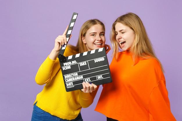 Dwie szalone młode blond siostry bliźniaczki dziewczyny w kolorowe ubrania, trzymając klasyczny czarny film, co clapperboard na fioletowej niebieskiej ścianie. koncepcja życia rodzinnego osób.