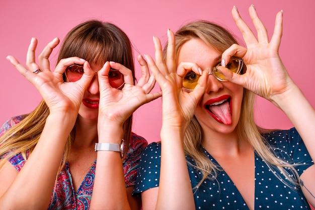 Dwie szalone śmieszne kobiety imitujące okulary za ręce, najlepsza przyjaciółka na imprezie, różowa ściana, stylowe sukienki, znaki gestów.