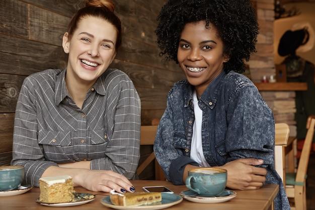Dwie szczęśliwe afrykańskie i kaukaskie lesbijki spędzają razem miło czas podczas lunchu w przytulnej kawiarni