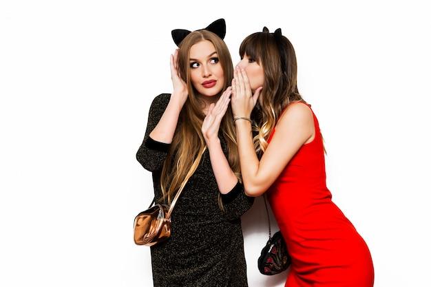 Dwie szczęśliwe atrakcyjne młode kobiety, śmieszne słodkie przyjaciółki, picie wina i dobra zabawa