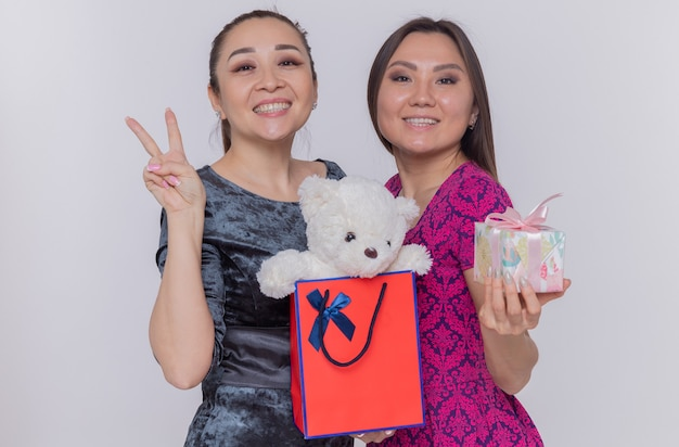 Dwie szczęśliwe azjatyckie kobiety trzymające papierową torbę z misiem i prezent z okazji międzynarodowego dnia kobiet uśmiechnięte wesoło, pokazujące znak v stojącego nad białą ścianą