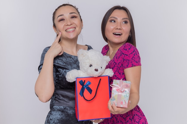 Dwie szczęśliwe azjatyckie kobiety trzymające papierową torbę z misiem i prezent z okazji międzynarodowego dnia kobiet uśmiechnięte wesoło stojąc nad białą ścianą