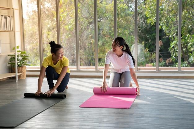 Dwie szczęśliwe azjatyckie kobiety w pozach jogi w studio jogi z sceną natura llight / koncepcja ćwiczeń / praktyka jogi / kopia przestrzeń / studio jogi