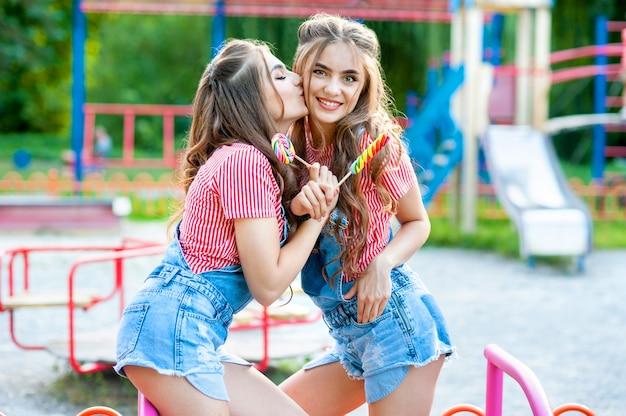 Dwie szczęśliwe bliźniaczki śmieją się i całują w dżinsowych kombinezonach z lizakami na placu zabaw