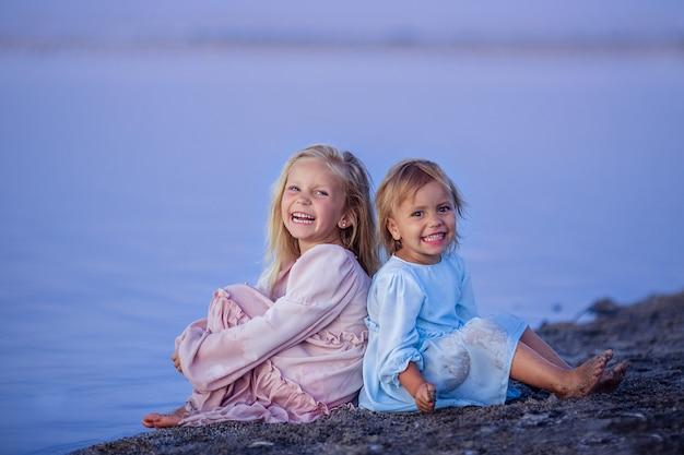 Dwie szczęśliwe dzieci dziewczynki siostry siedzą na brzegu rzeki o różowym zachodzie słońca.