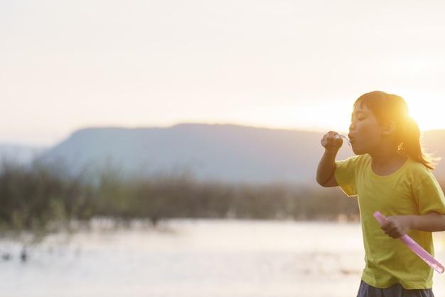 Dwie szczęśliwe dziewczynki biegają, bawiąc się bańkami mydlanymi na podwórku.