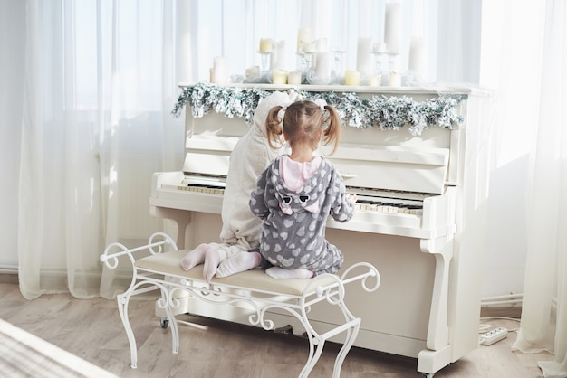 Dwie szczęśliwe dziewczynki w piżamie grają na pianinie w boże narodzenie