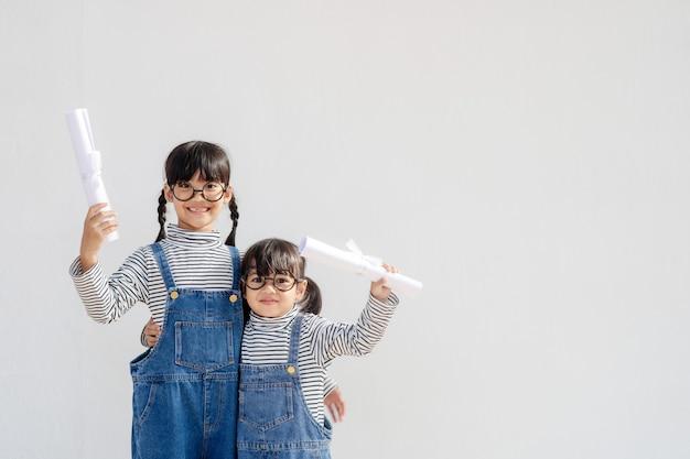 Dwie szczęśliwe dziewczynki z koncepcją ukończenia szkoły
