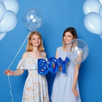 Dwie szczęśliwe dziewczyny, młode, w studio, trzymające niebieskie balony i balon z napisem chłopiec, niebieskie tło.