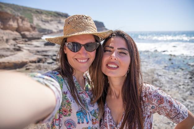 Dwie szczęśliwe dziewczyny na wakacjach robią sobie selfie na plaży